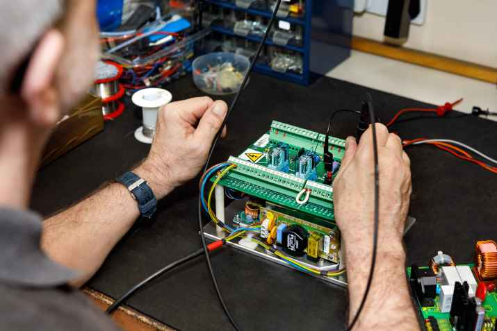 Engineer repairing a DC Power Supply